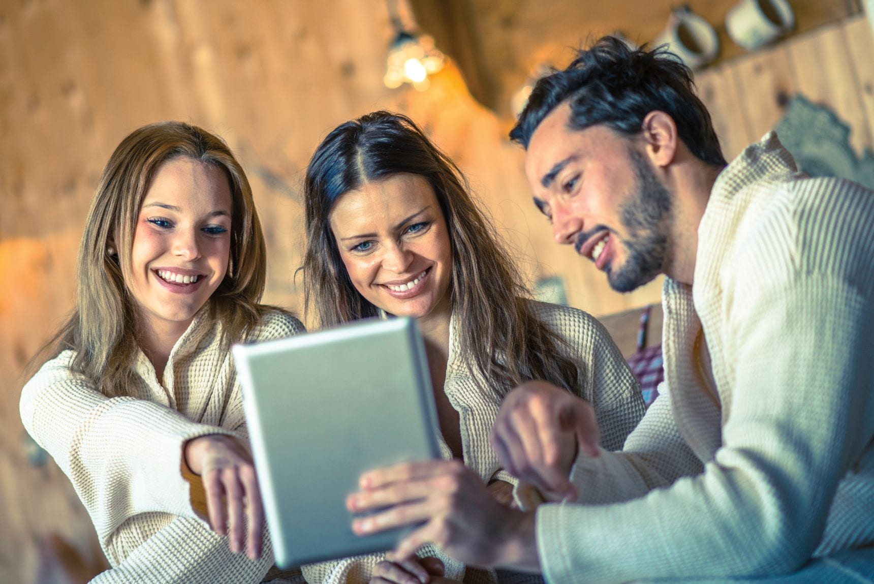 3 people happily looking at an IPad